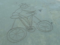 2015.09.13 Friendly bicycling cartoon on the sand of a Thai beach