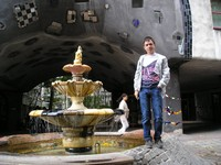 "2016.09.17 Vienna, the Hundertwasser's House (Hundertwasserhaus), its ""sagged"" arch with ""patches"", fountain with the inflow of a sidewalk"