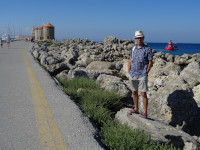 2019.06.06 On stone breakwaters of the outer side of the Mandraki Bay, with decorative windmills in the background.